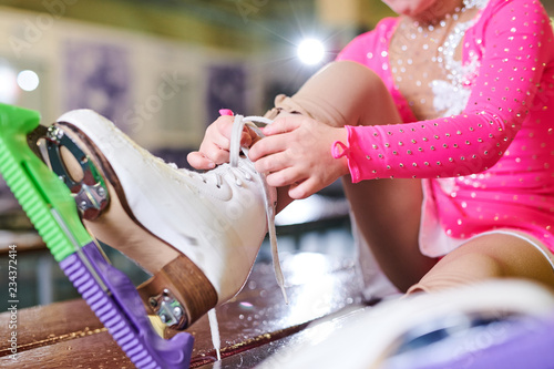 Close up of unrecognizable little girl tying figure skating shoe before practice, copy space