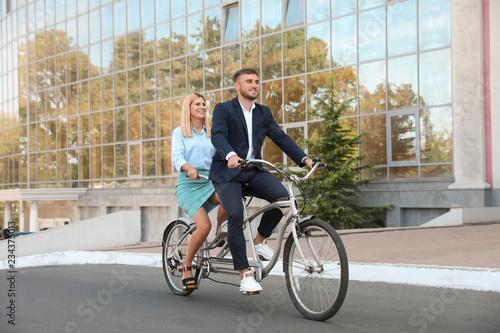 Couple riding tandem bike on city street