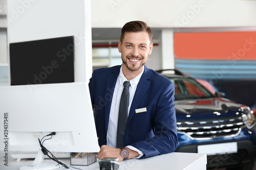 Photo Salesman working in modern car dealership. Buying new auto