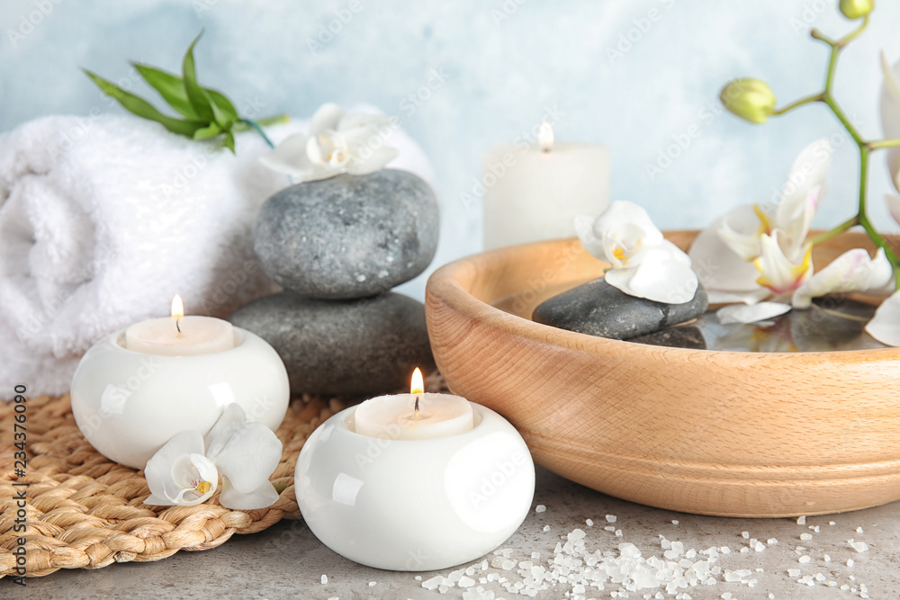 Composition with spa stones and candles on gray table