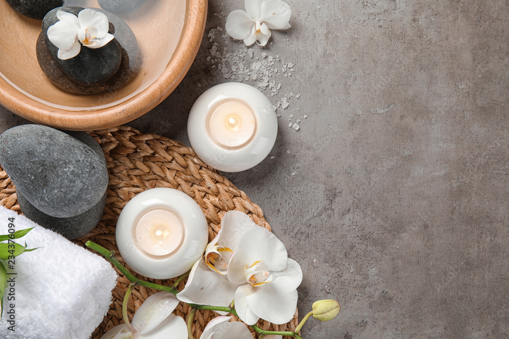 Flat lay composition with spa stones and candles on gray background. Space for text