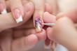 Leinwanddruck Bild - Closeup shot man making manicure to woman in beauty salon