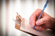 Man's Hand Puts Pen To Paper O...