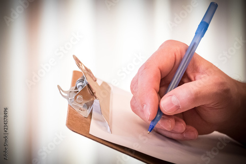Man's hand puts pen to paper on a clipboard, to sign a form, make a list, or fill out information Fototapete