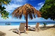 Sun chairs with thatched umbrella on a white sandy beach