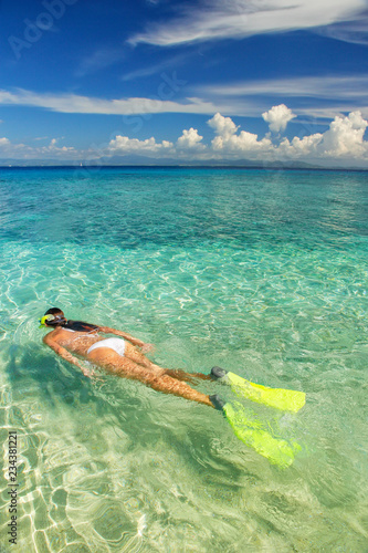 Papiers peints Recifs coralliens Young woman snorkeling in clear shallow water