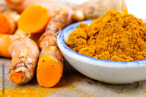 Cadres-photo bureau Condiment Turmeric roots and powder herb on wooden background.