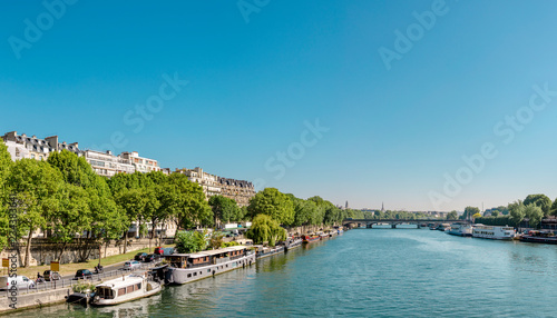 Manned barges moored to the coast of Seine river in Paris Wallpaper Mural