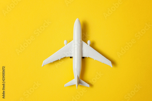 Fényképezés  Simply flat lay design miniature toy model plane on yellow colorful paper trendy background