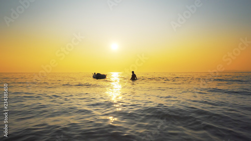 Fotografia Refugees silhouettes against sea sunset
