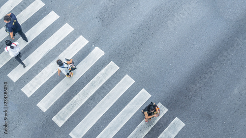 Obraz na płótnie From the top view of people walk on street pedestrian crossroad in the city street with the motorcycle drives pass road ,bird eye view