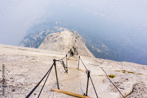 Fotografie, Tablou Looking down on the Half Dome cables on a summer day; smoke covering the sub dom