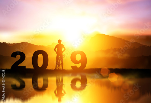 Silhouette bicycle in 2019 text on Water reflection sunset