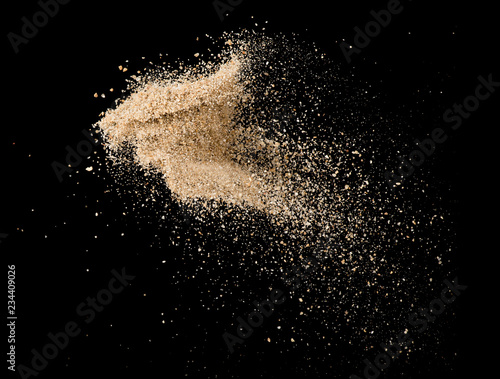 Sand flying explosion isolated on black background ,throwing freeze stop motion object design Wall mural
