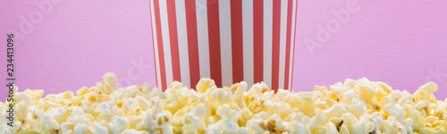 the bucket stands on a scattered popcorn, on a pink background