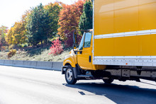 Small Yellow Semi Truck For Moving Local Cargo With Box Trailer Running On Wide Autumn Road