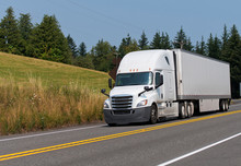 White Big Rig Semi Truck Transporting Dry Van Semi Trailer On The Road With Trees And Meadow Background