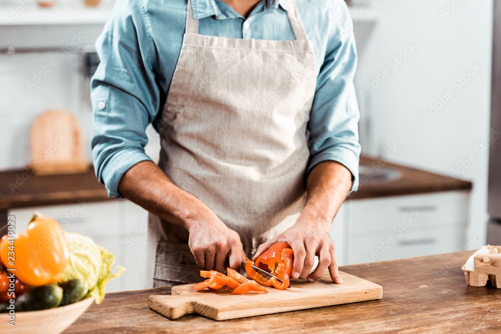 Fototapeta mid section of young man in apron cutting fresh pepper in kitchen