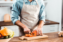 Mid Section Of Young Man In Apron Cutting Fresh Pepper In Kitchen