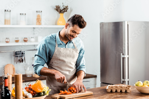 Leinwand Poster smiling young man in apron cutting fresh pepper in kitchen
