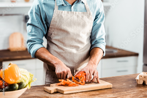 Slika na platnu mid section of young man in apron cutting fresh pepper in kitchen