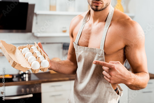 Canvastavla cropped shot of sexy bare-chested man in apron pointing with finger at egg carto