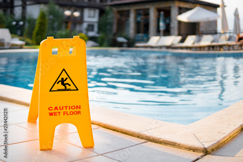 Leinwand Poster Wet floor sign by luxury hotel swimming pool