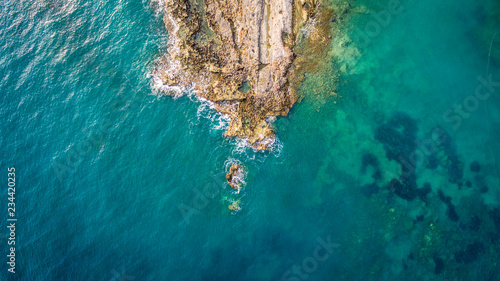 Photo  Aerial drone view of the ocean and waves crashing on rocks.