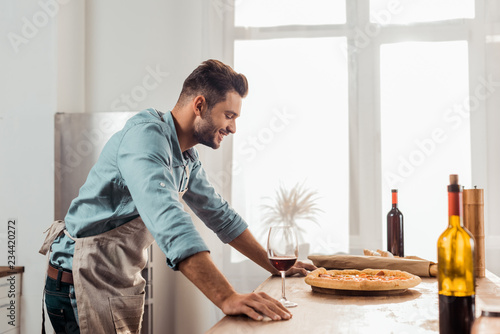 side view of smiling young man in aron looking at fresh homemade pizza Canvas Print