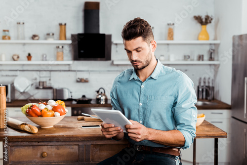 Fototapeta handsome young man using digital tablet while cooking in kitchen obraz