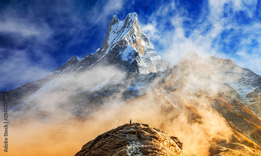 Fototapety, obrazy: Hiker reaches the summit of mountain peak of Machapuchare. A mountain in the Annapurna Himalayas of north central Nepal. View point from Mardi Himal base camp track