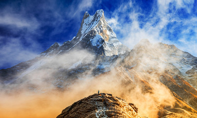 Hiker reaches the summit of mountain peak of Machapuchare. A mountain in the Annapurna Himalayas of north central Nepal. View point from Mardi Himal base camp track