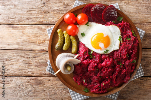 German cuisine Labskaus is a mashed potato, corned beef and beetroot with fried egg, pickled cucumbers and rollmop close-up. horizontal top view