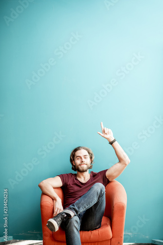 Photo  Portrait of a young caucasian bearded man with long hair showing with hands on the colorful background sitting on the chair