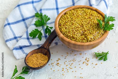 Tuinposter Kruiderij Grain mustard in a bowl and wooden spoon.