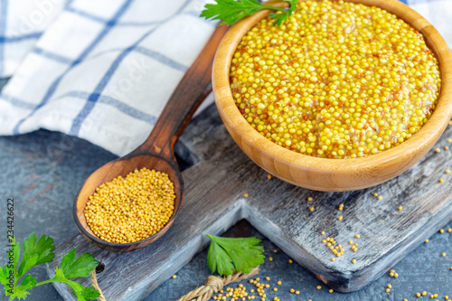Tuinposter Kruiderij Spicy mustard seed in a wooden bowl.