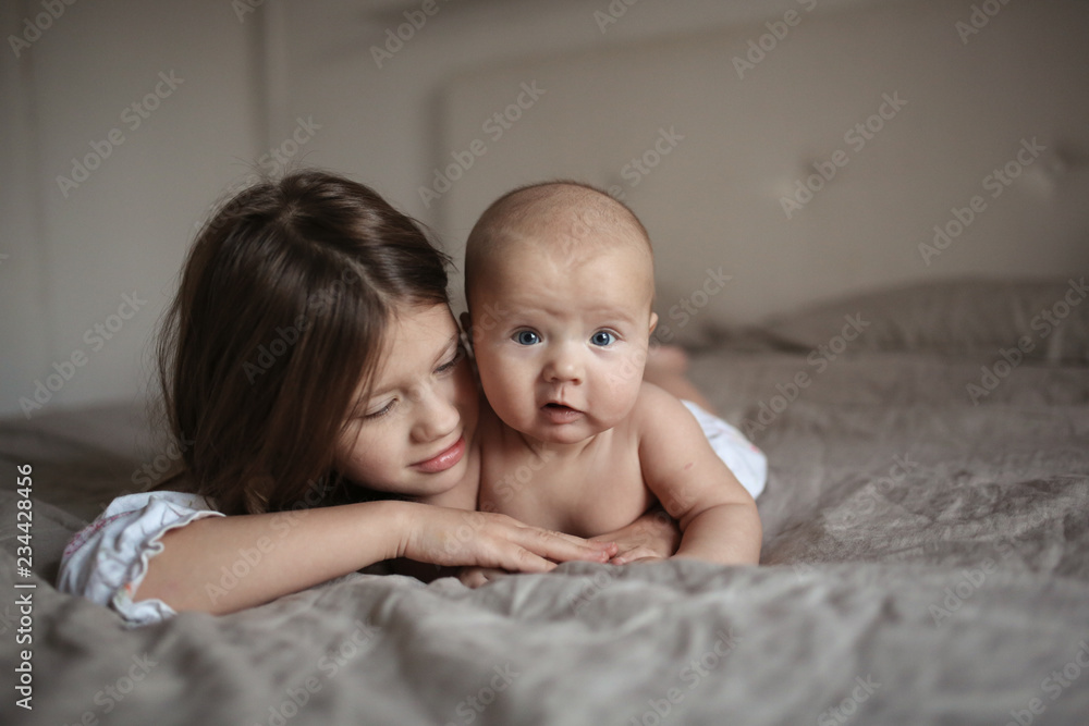 Fototapety, obrazy: older sister and naked baby 5 months on bed