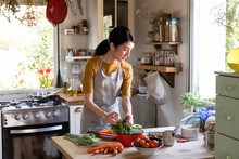 Asian Woman Busy Cooking In The Kitchen