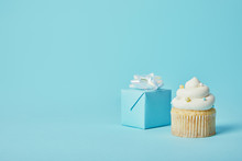 Gift Box With White Bow And Delicious Cupcake On Blue Background