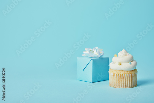 Gift box with white bow and delicious cupcake on blue background Canvas Print
