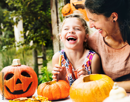 Young cheerful girl carving pumpkins with her mom Wall mural
