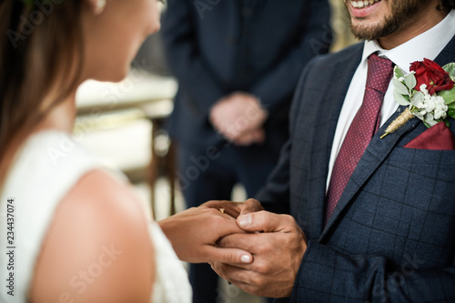 Fotografie, Obraz  Groom putting on the wedding ring on his bride