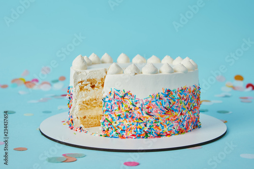 Delicious cut cake cut on blue background Fotobehang