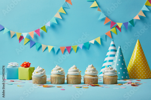 Delicious cupcakes with sugar sprinkles, party hats and gifts on blue background Wallpaper Mural