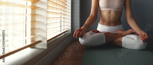 young woman practices yoga ...