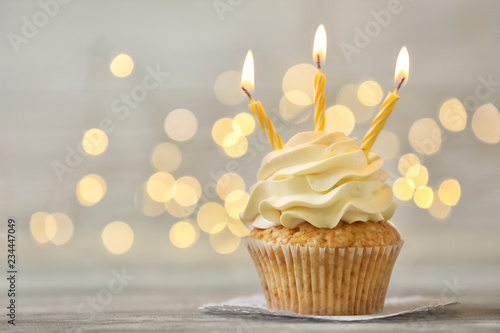 Photo  Delicious birthday cupcake with burning candles on grey table  against blurred l