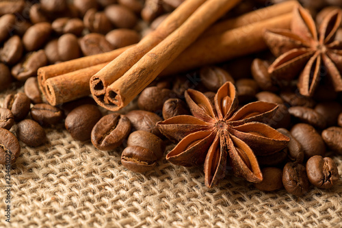 Fototapeta Coffee beans, anise and cinnamon on brown burlap. Close up obraz