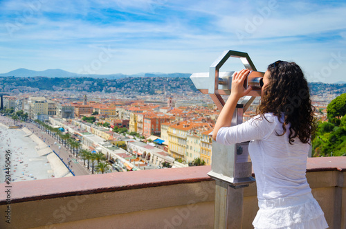 Fotobehang Nice Tourist enjoying view over panoramic city of Nice in France looking on coin operated binocular