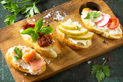 Antipasti snacks close-up set for Wine. Variety Brushetta with Soft Cheese, Pear, Radish, Salmon and Dried Tomatoes served on a rustic wooden board on a stone table.