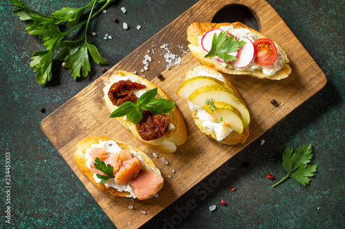Italian Antipasti snacks set for Wine. Variety Brushetta with Soft Cheese, Pear, Radish, Salmon and Dried Tomatoes served on a rustic wooden board on a stone table. Top view flat lay background.